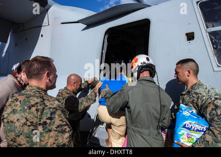 Marines with Marine Medium Tiltrotor Squadron 262, 1st Marine Air Wing, assist a Filipino woman and her pre-mature - Stock Photo