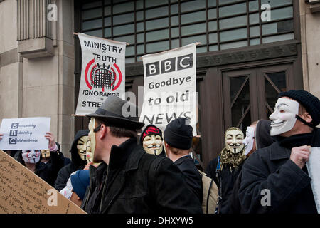 London, UK. 16th November 2013. Protesters wearing Anonymous masks hold up placards and banners outside BBC Broadcasting - Stock Photo