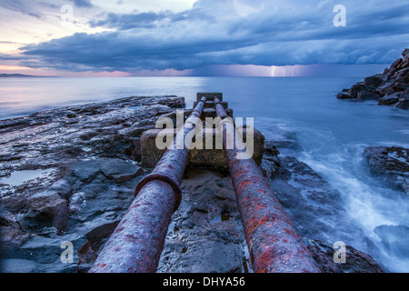 Pipes heading into the ocean with lightening in background - Stock Photo