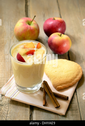 Yogurt with pieces of apple and peach in glass on wooden table - Stock Photo