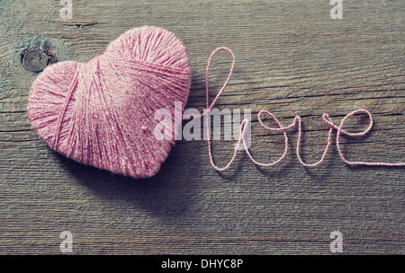 Pink clew in shape of heart and word 'love'on vintage wooden background - Stock Photo