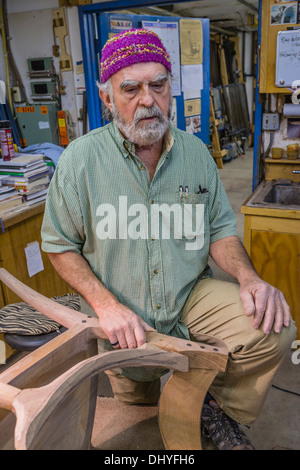 Larry White, fine woodworker, stands by a chair he is creating in the shop of the famous artist/woodworker Sam Maloof. - Stock Photo