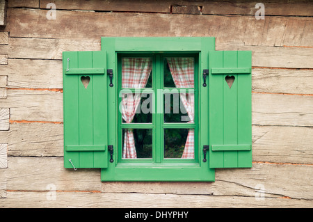 Wooden window with hearts on traditional log cabin - Stock Photo