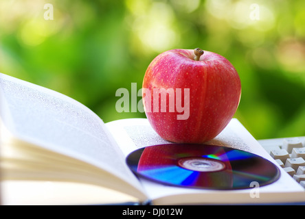 Ripe apple, dvd, and open book - Stock Photo