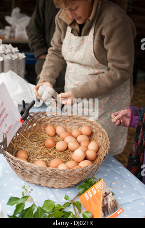 A female stall holder being paid by a customer that is purchasing some free range chickens eggs from a market stall - Stock Photo