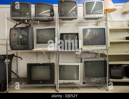 Second-hand CRT analog television sets are seen lined up for sale in a thrift store in New York - Stock Photo