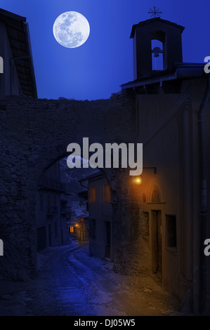 Night view of narrow street between old houses under the sky with full moon in town of Tende, France. - Stock Photo