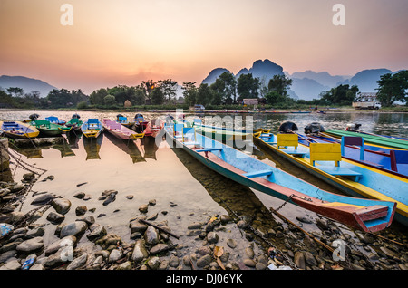 Boats on river in Vang vieng at sunset - Stock Photo