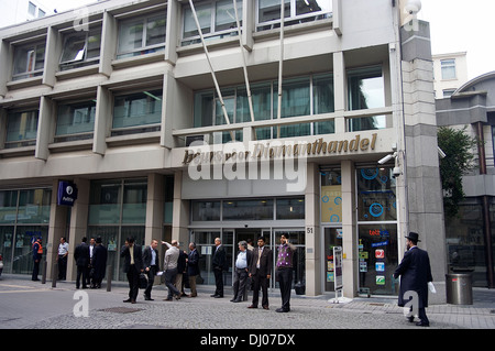 Businessmen in front of the Beurs voor Diamanthandel, a world center of the diamond trade located in Antwerp's diamond - Stock Photo