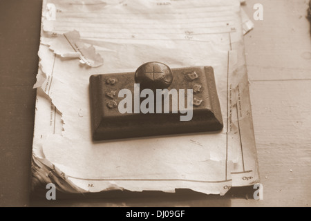 Antique paperweight on the top of the old pile of papers - Stock Photo