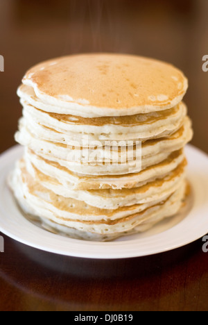 A stack of 10 fresh, hot buttermilk pancakes, with the steam still rising from the top. - Stock Photo