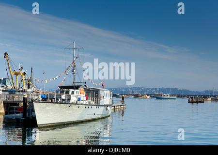 Brixham marina Devon with large boat Torbay England UK on blue sky day - Stock Photo