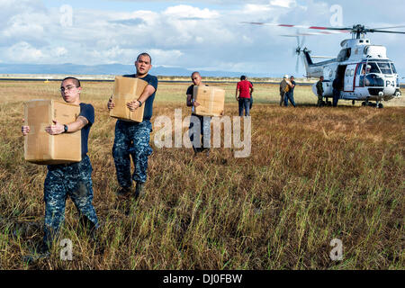 US Navy sailors unload relief supplies that were airlifted ashore to by a SA-330J Puma helicopter in the aftermath - Stock Photo