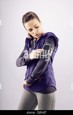 Young caucasian woman wearing earphones listening to music on mp3 player. Female runner listening music on grey - Stock Photo