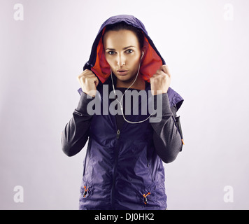 Portrait of beautiful young woman in sportswear looking at camera. Confident female runner in hoodie against grey - Stock Photo