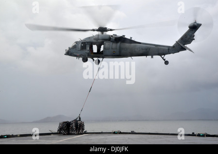 A U.S. Navy MH-60S Seahawk helicopter assigned to Helicopter Sea Combat Squadron (HSC) 25 transports a pallet of - Stock Photo