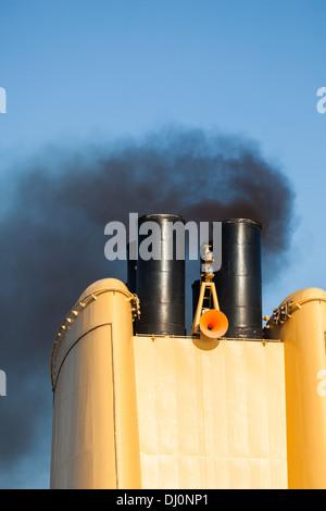 Ship discharging black smoke - Stock Photo