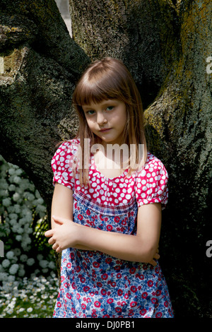 little girl leaning against a tree