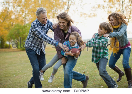 Happy multi-generation family playing American football in park - Stock Photo