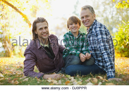 Portrait of happy boy with father and grandfather sitting at park - Stock Photo