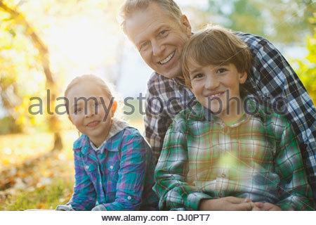 Portrait of happy grandfather with grandchildren sitting in park - Stock Photo