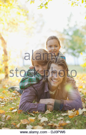 Portrait of happy father with children lying on grass at park - Stock Photo