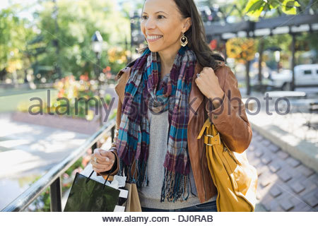 Woman with shopping bags walking outdoors - Stock Photo