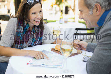 Couple reading map at outdoor cafe - Stock Photo