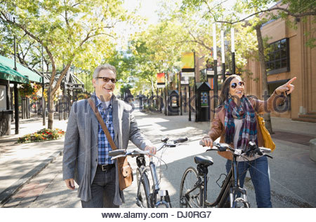 Smiling couple walking on street with bicycles - Stock Photo
