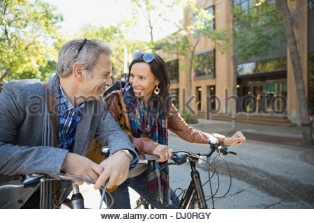 Smiling couple with bicycles looking at each other - Stock Photo