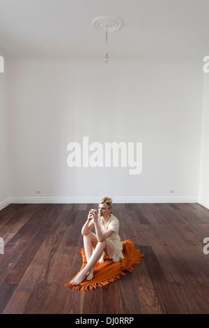 woman sitting on the floor in an empty room - Stock Photo