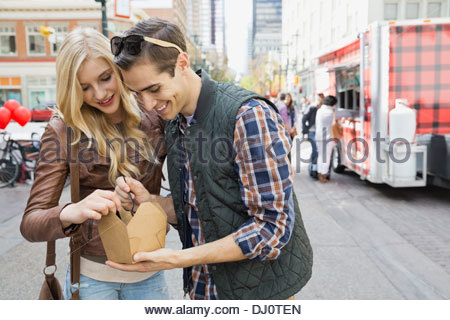 Couple standing outdoors sharing a meal from a food truck - Stock Photo
