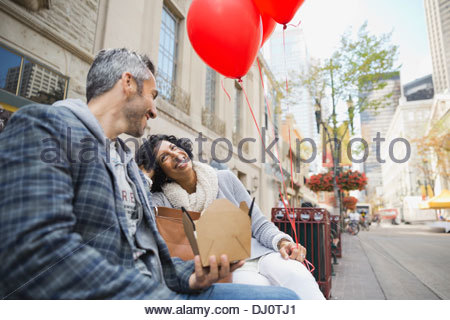 Couple sitting on city bench sharing a meal - Stock Photo