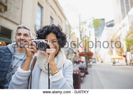 Woman photographing with man on city street - Stock Photo