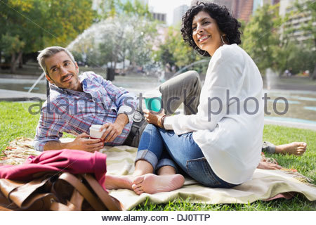 Couple relaxing in city park with coffee - Stock Photo