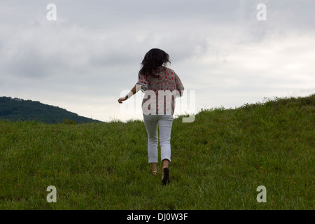 Young Chinese woman seen from behind as she runs away from the camera up a green hill. - Stock Photo
