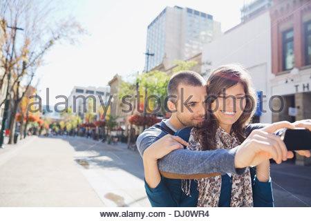 Loving couple taking self portrait on city street - Stock Photo