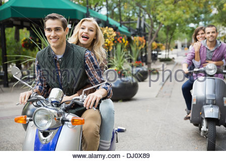 Two couples riding scooters on city street - Stock Photo