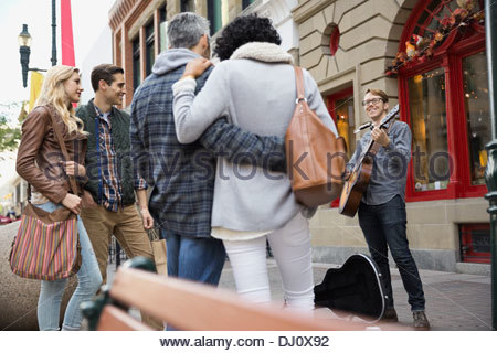 Street musician playing music for pedestrians - Stock Photo