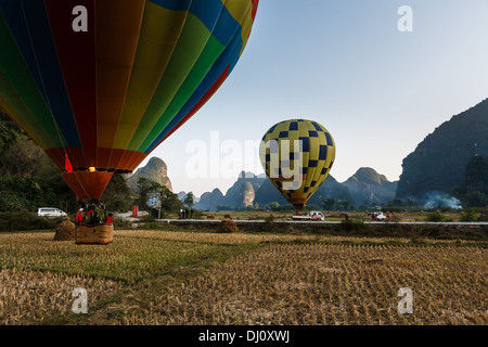 Two colorful hot air balloons take off from a field along the Li River Valley in Yangshao, China - Stock Photo