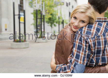 Portrait of woman embracing man on city street - Stock Photo