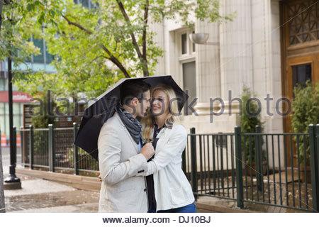 Couple walking on city street with umbrella - Stock Photo