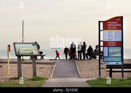People gathering on Shoreham Bathing Beach on a Saturday afternoon in late Autumn - Stock Photo