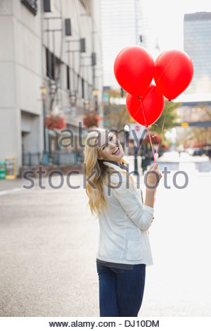 Woman standing on city street holding red balloons - Stock Photo