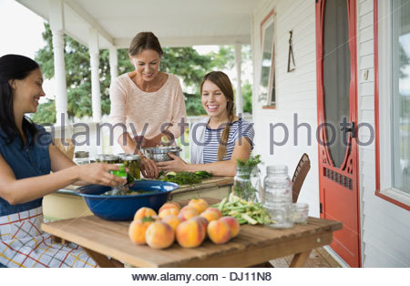 Female family members preparing to can vegetables - Stock Photo