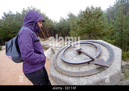 Young woman looking at compass on a rock while hiking in Peñalara, highest mountain peak in the mountain range - Stock Photo