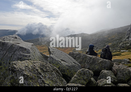 Hikers in Peñalara, highest mountain peak in the mountain range of Guadarrama, Spain - Stock Photo