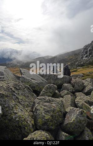 Hikers in Peñalara, highest mountain peak in the mountain range of Guadarrama, Spain - Stock Photo