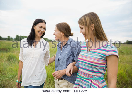 Female family members walking through field - Stock Photo