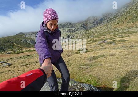 Young woman hiking in Peñalara, highest mountain peak in the mountain range of Guadarrama, Spain - Stock Photo
